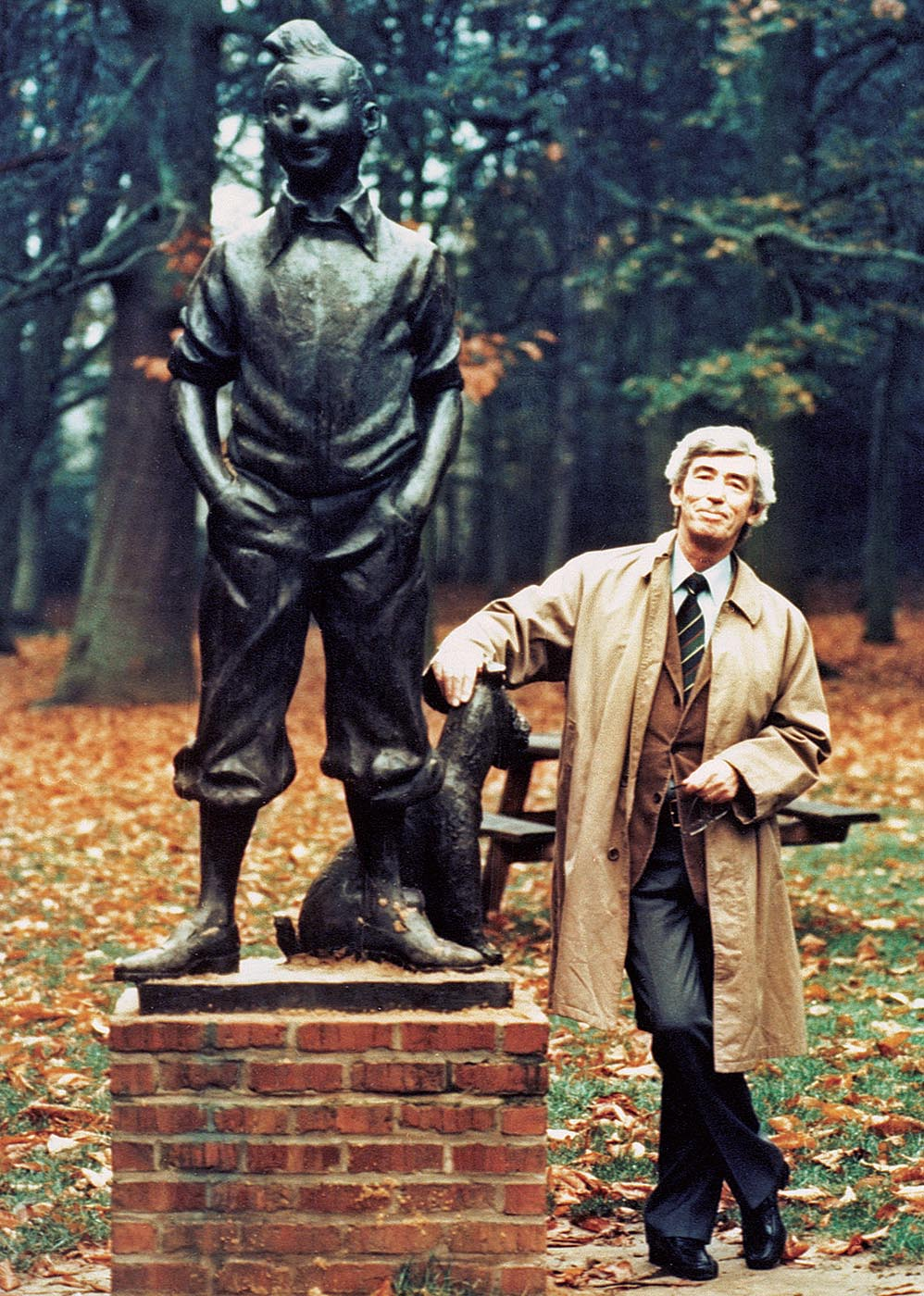 Hergé poses next to the bronze statue that was made by the Belgian artist Nat Neujean